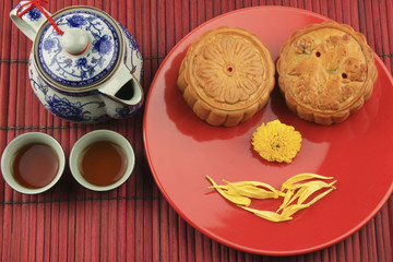 Moon cakes and tea on a red mat