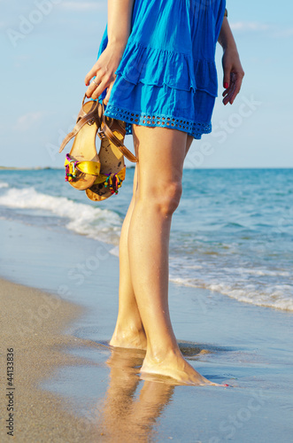 Woman holding her sandals on a beach