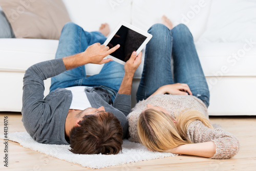mann zeigt seiner freundin etwas am tablet