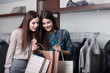 Two girlfriends buy presents in a sale