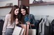 Two girlfriends buy presents in a sale