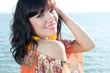 Smiling young woman relaxing on the shore, horizontal shot