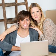 glückliches paar mit laptop beim umzug