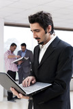 young Businessman holding laptop with colleagues in background