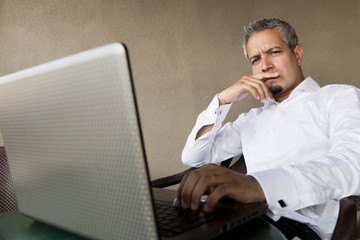 portrait of a handsome indian businessman using laptop