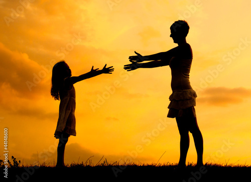 Silhouettes of mother and daughter meeting on the meadow