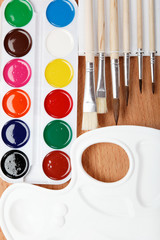 Paint, palette and brushes on a wooden table.