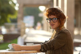 Hipster girl sitting in a cafe outdoors poster