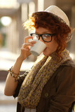 Hipster girl drinking coffee outdoors poster