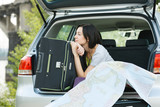 Daydreaming female sitting in the trunk of a car