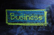 The word Business ; handwritten with white chalk on a blackboard