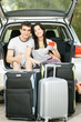Couple sitting in the opened car bloom with suitcases