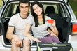 Couple sitting in opened car bloom holding empty credit card