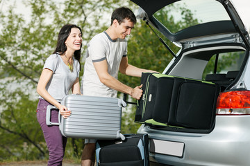 Happy couple going to vacations, loading their car boot