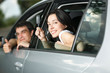 Young couple showing the car keys sitting in new car
