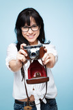 cute young girl photographer holding rretro camera is a hipster poster