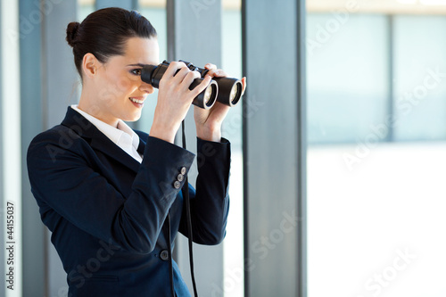 businesswoman looking outside office window with binoculars