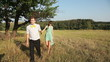 Young couple walking on the yellow grass