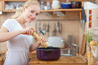 young woman cooking in the kitchen- seasoning into a pot