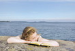Portrait of a girl lying on the rock with book.