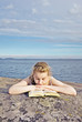 Portrait of a girl lying on the rock and reading book.