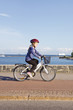 Little girl riding bicycle by the sea.