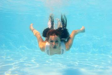 Woman wearing a white dress underwater