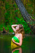 blonde young woman standing waist-deep water in the river in a g