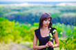 thin brunette woman holding flowers on a green field open backgr