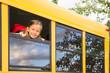 Little Schoolgirl looking through a Schoolbus Window