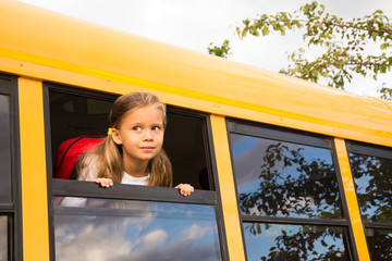 Little Schoolgirl looking through a Schoolbus Window