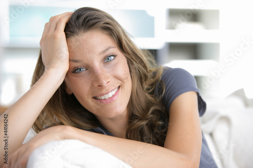Portrait of a young woman smiling on white couch