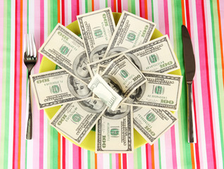 Banknotes on the plate on striped tablecloth close-up