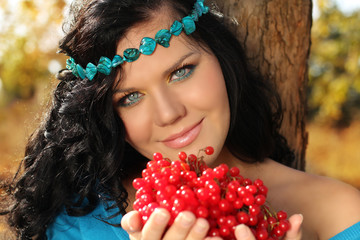 Portrait of beautiful Woman on rest with berry in her hands
