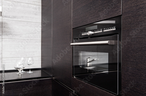 Part of black hardwood kitchen with build-in microwave oven