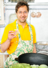 Handsome mature man is cooking at his kitchen.
