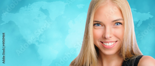 Young beautiful woman standing against worldmap background. Inte