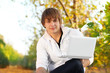 Young man with laptop in park, outside seasonal