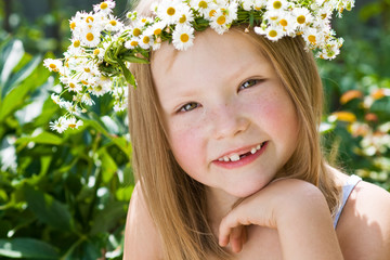 A pretty little girl in wreath of flowers