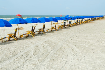 Beach lounge chairs with umbrellas.