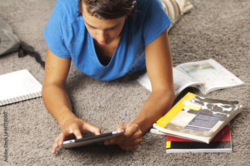 Young man is using a tablet computer while studying