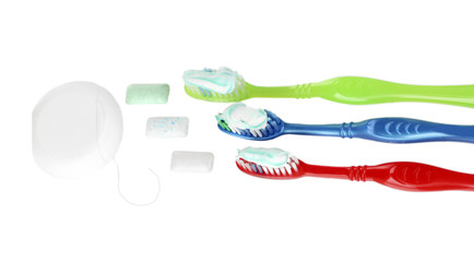 Toothbrushes, dental floss and chewing gum isolated on white