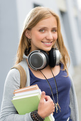 Teenage girl outdoor holding books with headphones