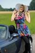 Junge blonde Frau lehnt sich an ein Cabrio