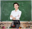 Smiley chemistry teacher surrounded with chemical glassware