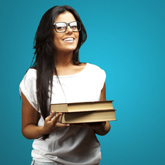 portrait of young girl holding books over blue background