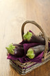 Raw aubergines or eggplants in basket on wooden backround.