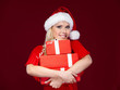 Woman in Christmas cap hands presents wrapped with red paper