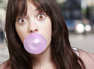 young girl with a pink bubble of chewing gum against a street ba