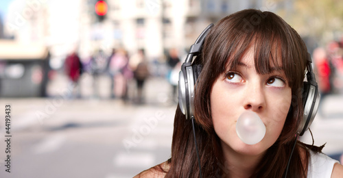 portrait of young woman listening to music with bubble gum again